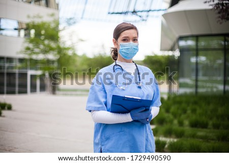 Young female EMS key worker doctor in front of healthcare ICU facility,wearing protective face mask holding medical patient lab health check form,COVID-19 pandemic outbreak crisis PPE shortage in UK