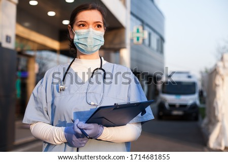 Young female EMS key worker doctor in front of healthcare ICU facility,wearing protective PPE face mask equipment,holding medical lab patient health check form,UK US COVID-19 pandemic outbreak crisis