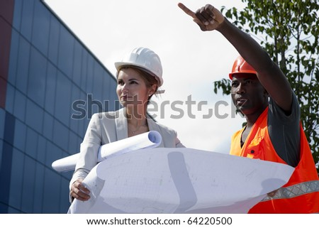 Young female engineer discussing a building project with a construction worker - stock photo