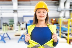 Young female engineer making powerful super hero gesture by pulling vest as professional wonder woman concept on indoor factory background