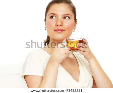 Young female enjoing her cup of tea and looking at copyspace isolated on white background
