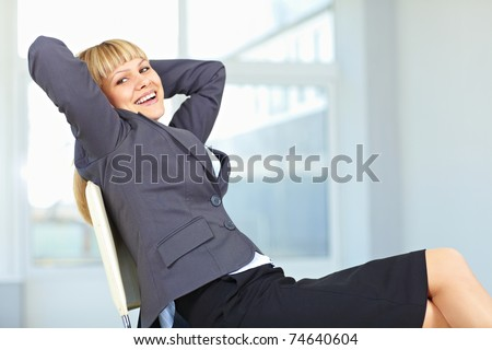 Young female executive relaxing in an office chair with hands behind head