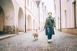 Young female fancy-dressed using a face mask as a coronavirus spreading prevention walking with her beagle dog on deserted old European squares and streets. Global COVID-19 pandemic concept image.