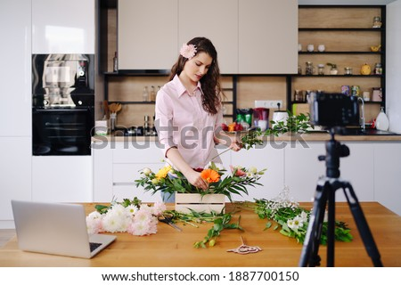 Young female florist record video tutorial of floral compositions design on camera, woman interior designer shoot vlog on camera, arrange handmade house flower decorations