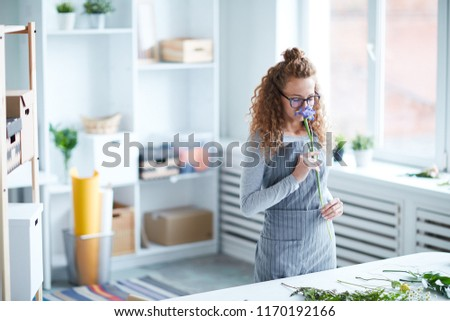 Young female florist smelling iris flower on long stem while standing by desk and working