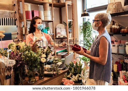 Young female florist with mask working in flower shop, selling flower arrangement to senior woman. Photo stock ©