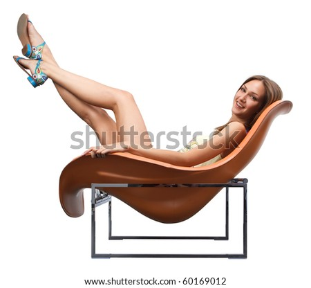 Young female fooling in the fashionable chair stretching out her legs