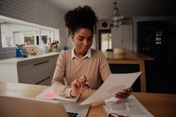 Young female freelancer analysing documents and comparing growth while working on laptop at home during covid-19 lockdown