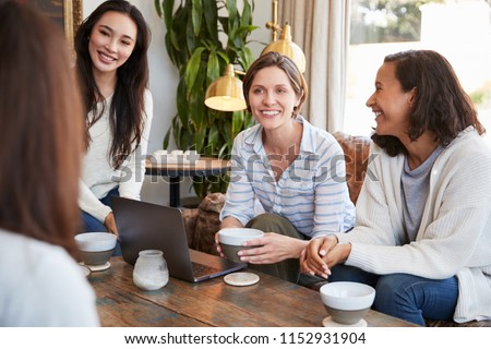 Young female friends talking over coffee at a coffee shop