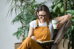 Young female gardener in glasses wearing overalls, resting after work, sitting on wooden chair in home greenhouse, holding reusable foldable coffee/tea mug, smiling and reading book on her knees.