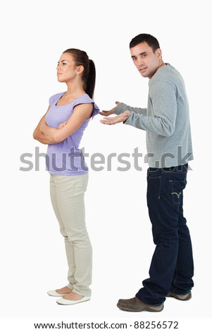 Young female giving her boyfriend the cold shoulder against a white background