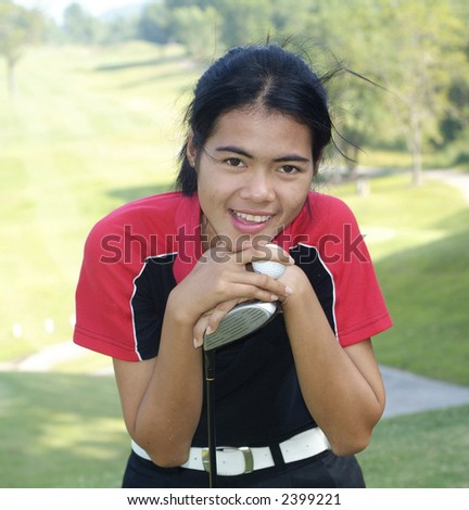 Young, female golf player smiling, holding golf club and ball, with fairway in the background.
