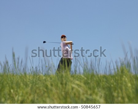 Young female golfer driving ball, low angle view
