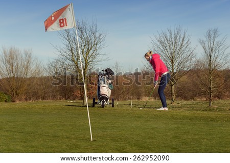 Young Female Golfer in a Golf Sports Training, Wearing Jacket and Jeans, chipping Golf Ball on Cup with Flag