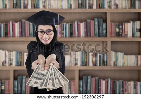 Young female graduate holding money at library
