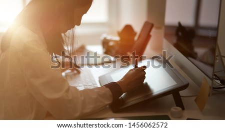 Young female graphic designer sketching on her project with modern creative work place   #1456062572