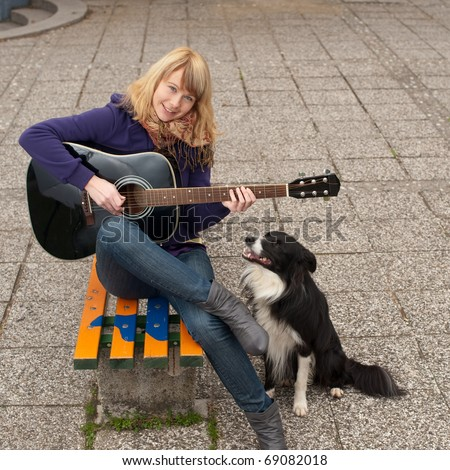 Young female guitar performer posing with her instrument and her dog