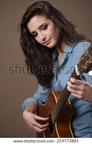 Young female guitarist performing with acoustic guitar