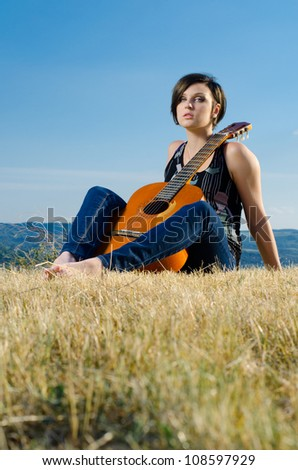 Young female guitarist posing with acoustic guitar on field.