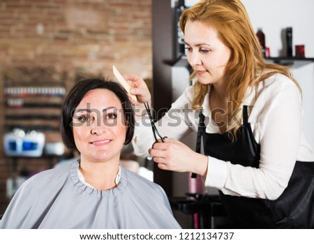 Young female hairdresser doing fashionable hairdo to adult woman with scissors and combs in hairdress salon