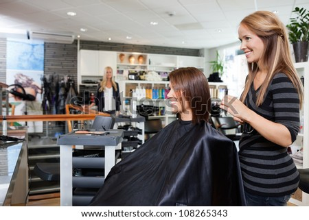 Young female hairdresser standing behind customer's chair after giving a haircut