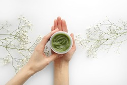 Young Female hands hold a jar of green natural cream for face or body. organic natural skincare products and flower on white. Packaging of lotion or cream. Beauty cosmetic skincare concept.