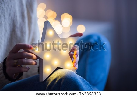 Young female hands holding glowing white LED star on warm bokeh background indoor. Festive Christmas illumination, holiday atmosphere.