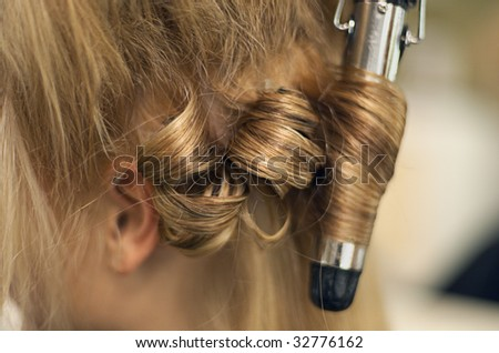 Young female having her hair styled in a hairdressing salon