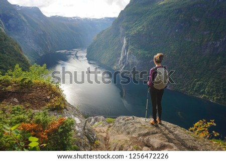 Young female hiker standing in awe and admiring 7 sisters waterfall in Norway, Geiranger Fjord, o a summer day #1256472226
