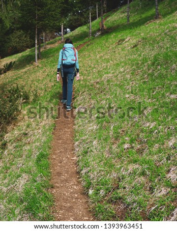 Young female hiker walking up hill on path in the forest in spring #1393963451