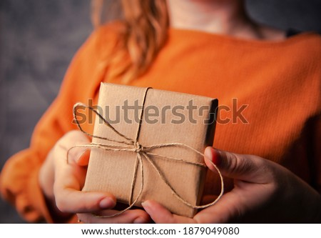 Young Female holding a kraft gift box, wrapped in plain brown paper, Valentines day, Birthday, Mothers Day present or gift concept selective focus, dark background closeup ストックフォト ©