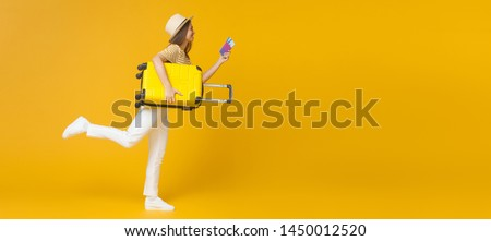Young female holding suitcase and tickets running for journey isolated on background, copyspace on right