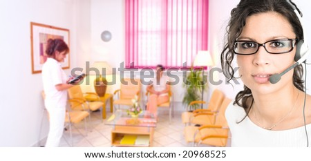 Young female hospital receptionist receiving phone calls in headset with clinic waiting room in background.