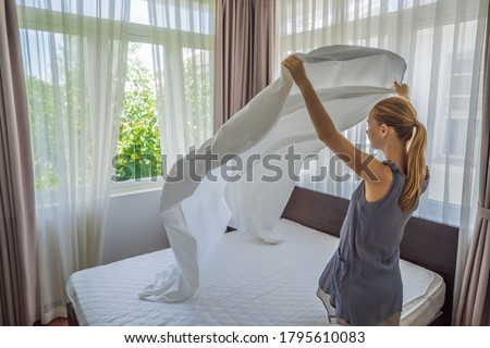 Young Female Housekeeper Changing Bedding In Hotel Room Photo stock ©