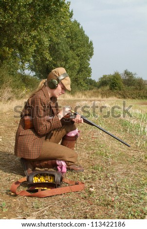 Young female hunter loading a gun on the field