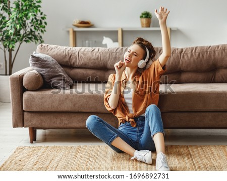 Young female in casual outfit listening to music in headphones and singing while sitting on floor near sofa and having fun at home
