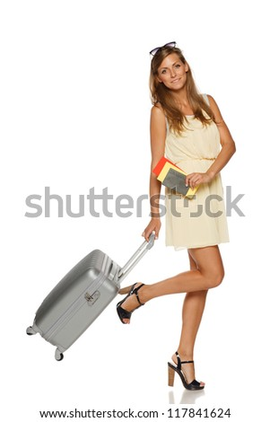 Young female in elegant light dress standing with travel bag, holding passport and tickets,over white background