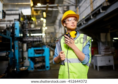 Young female in protective uniform, helmet and eyeglasses holding walkie-talkie while working at plant