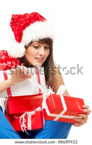 Young female in Santa hat sitting on the floor and unwrapping her Xmas gifts, over white background