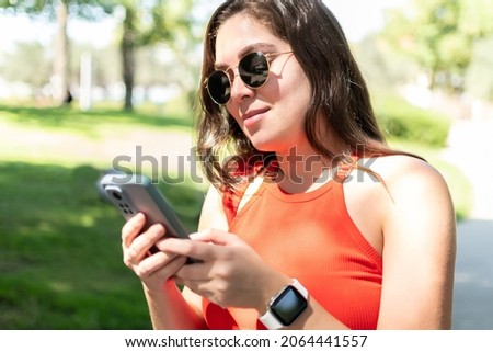 Young female in stylish sunglasses writing message on her smart phone.