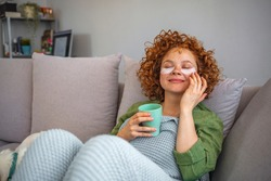 Young female in the living room drinking coffee while wearing facial mask for beauty treatment. Relax, recharge, reflect, detox and beautify. Leisure time at home