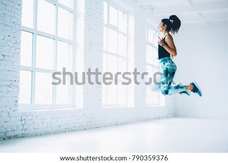 Young female in tracksuit jumping doing aerobics cardio exercises for losing weight and training strength,sportswoman doing leaps burning calories on pilates workout enjoying active lifestyle #790359376