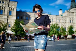 Young female in trendy sunglasses looking at location map choosing route for travel walking in city, Caucaisan hipster girl with orientation paper exploring town during solo getaway vacations