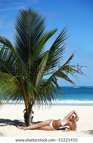 Young female in white bikini enjoying sunny day under palm tree on the tropical beach