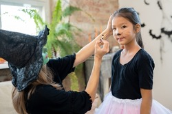 Young female in witch hat and black pullover applying halloween makeup on face of cute Asian girl in front of camera