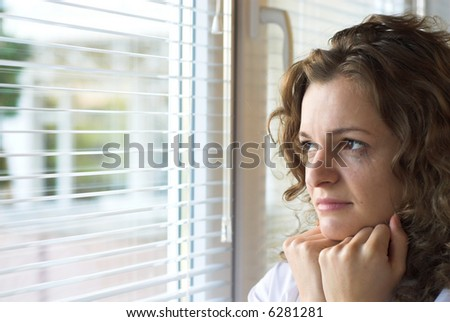 Young female is crying near window with jalousie