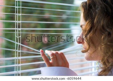 Young female is waiting with hope near window