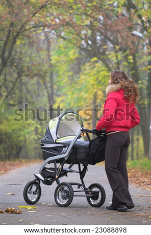 Young female is walking in park with baby carriage
