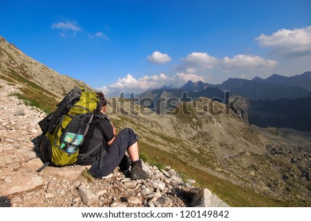 Young female is walking on footpath in mountains.