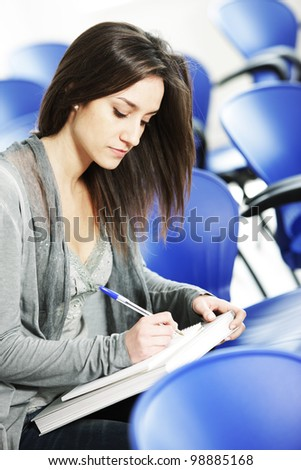Young female is writing notes and planning her schedule